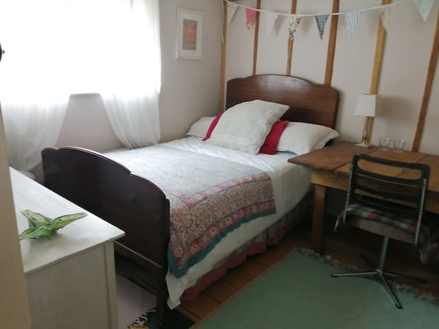 The Guest Room with double bed, drawers and view of the meadow bank.
