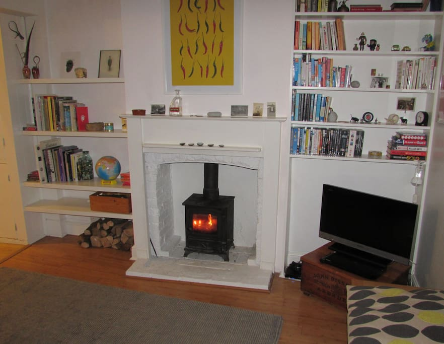 Comfortable sitting room with tv, leather sofa and wood burning stove