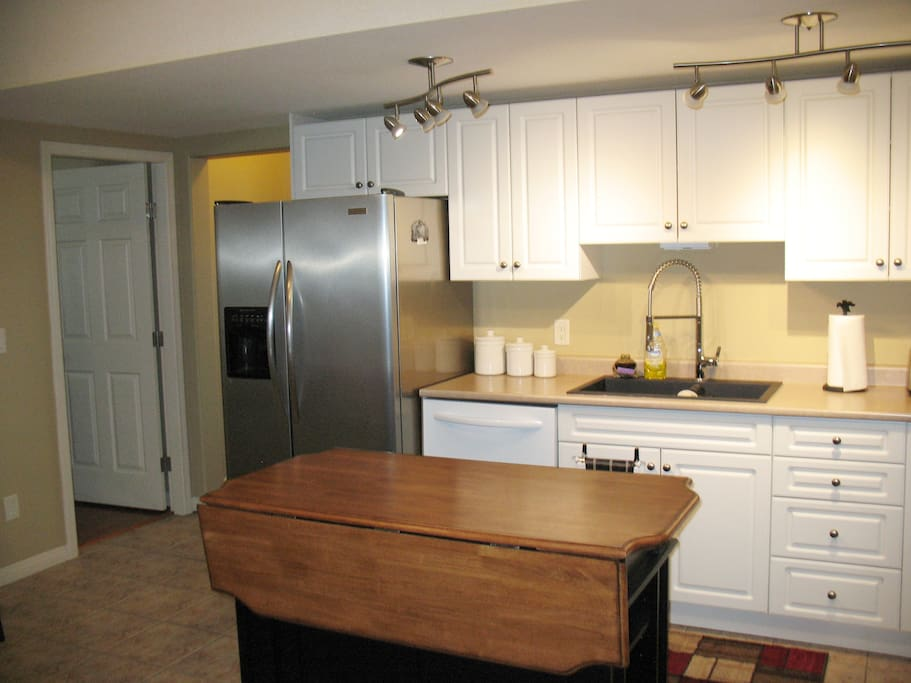 large kitchen with island, full fridge with water and ice dispenser.