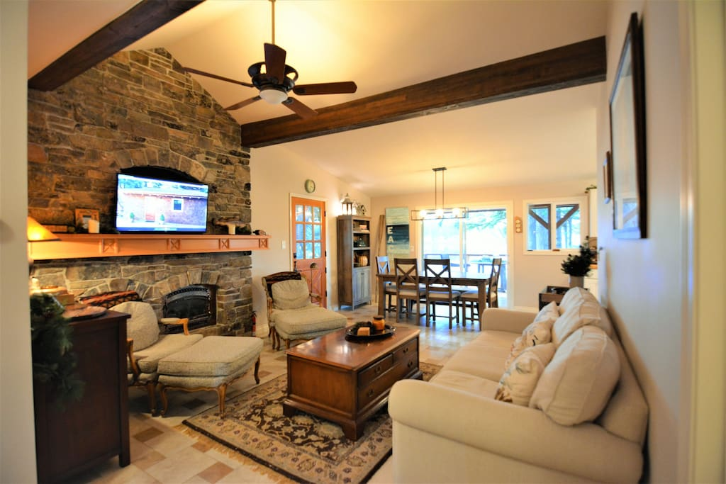 Living room with stone fireplace and vaulted ceilings.