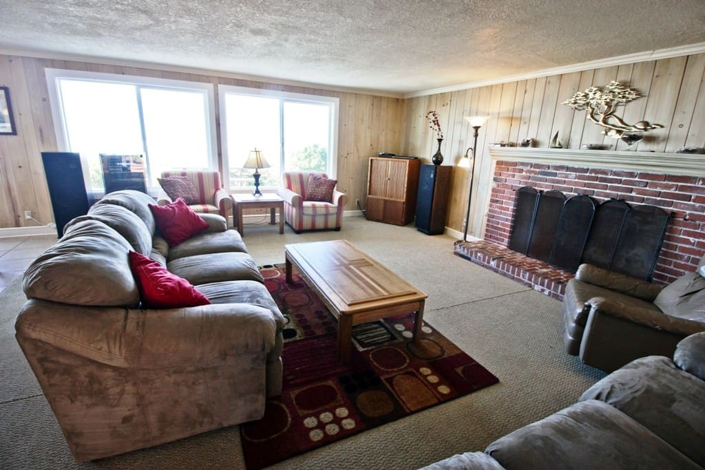 Lower level living room with cable TV/DVD, CD/Tape/Record player stereo, wood burning fireplace, two couches, two arm chairs, leather recliner and spectacular ocean front views