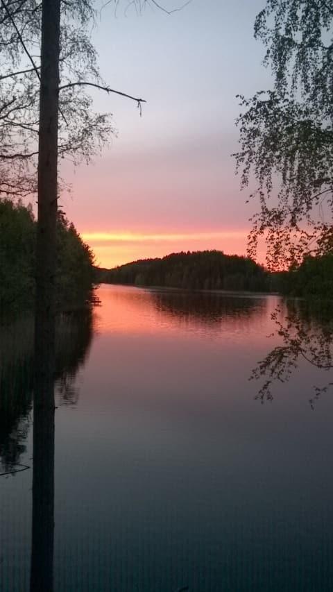 Уютна кабіна з бревнами на березі озера з сауною, що палить дерево