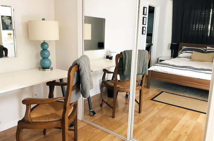 Bedroom desk and mirrored closet.