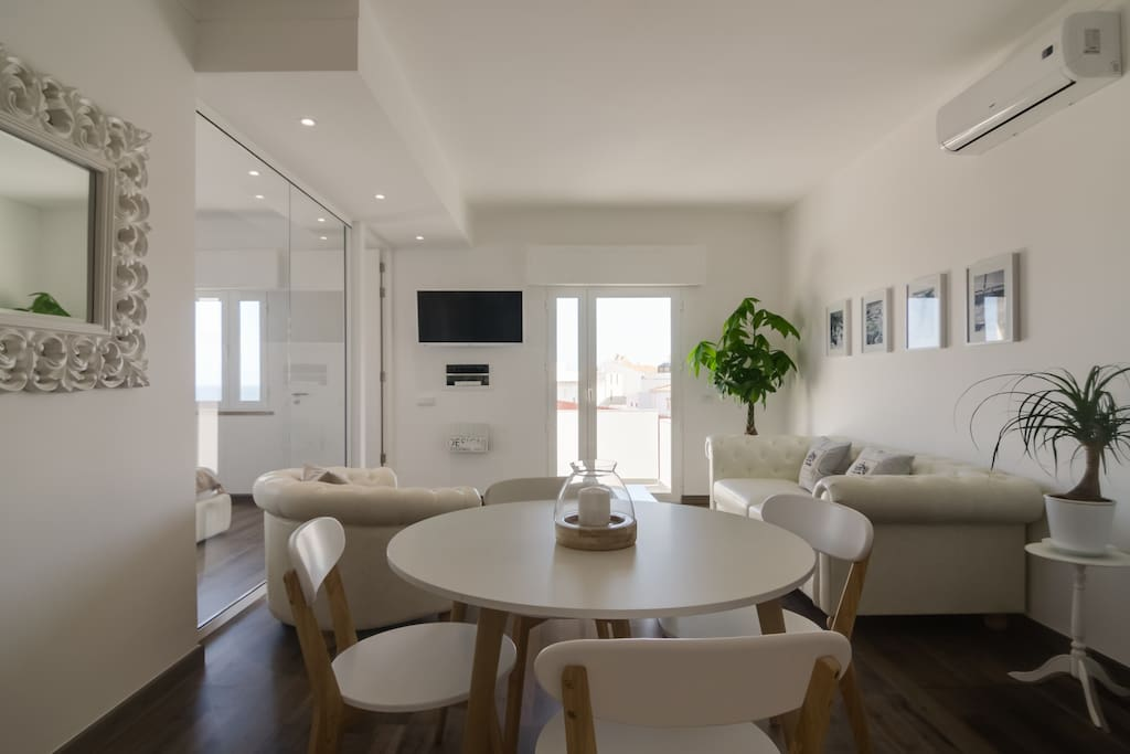 Bright living room with dining area, air conditioner  and balcony