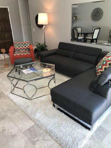 Recently redecorated mid-century modern living room with 65 inch flat screen television. Freshly painted throughout.