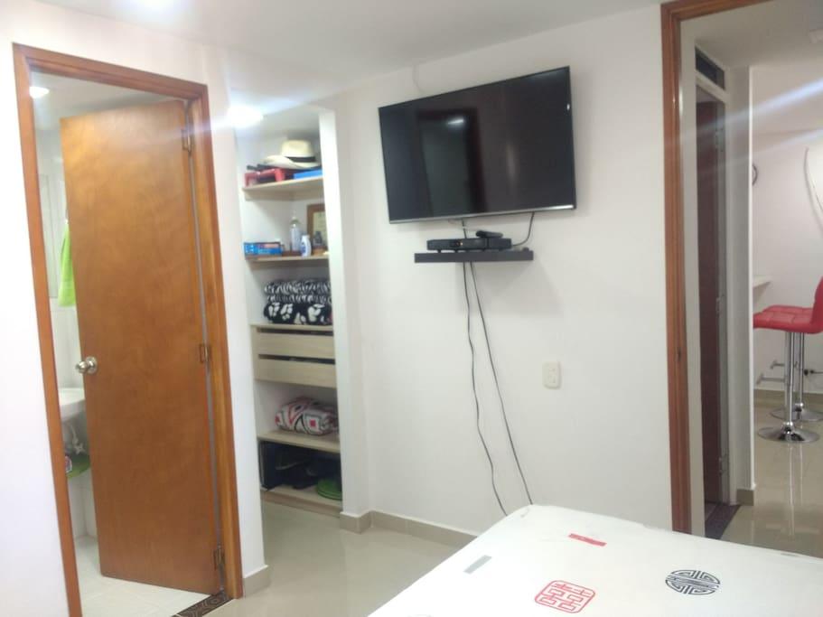 Baño al interior de la habitación, closet y smart TV.