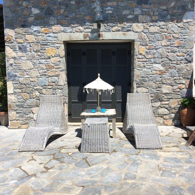 Voorkant met 2 ligstoelen. Grote parasol voorradig. Ideaal om te genieten van de zon en het uitzicht over de baai.
