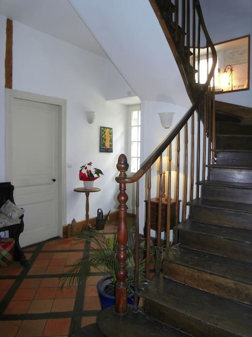 the inner hall with hand carved staircase and traditional Perigordian tomette floor inlaid with oak