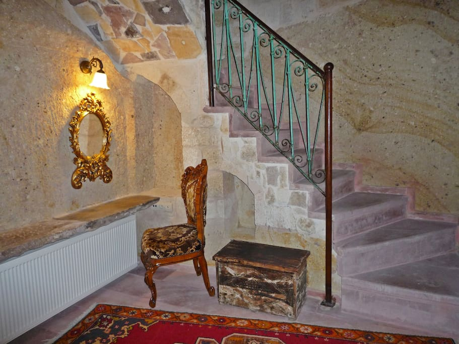 Roman suite cave bedroom, stone beauty table, stairs up to ground level sitting room.