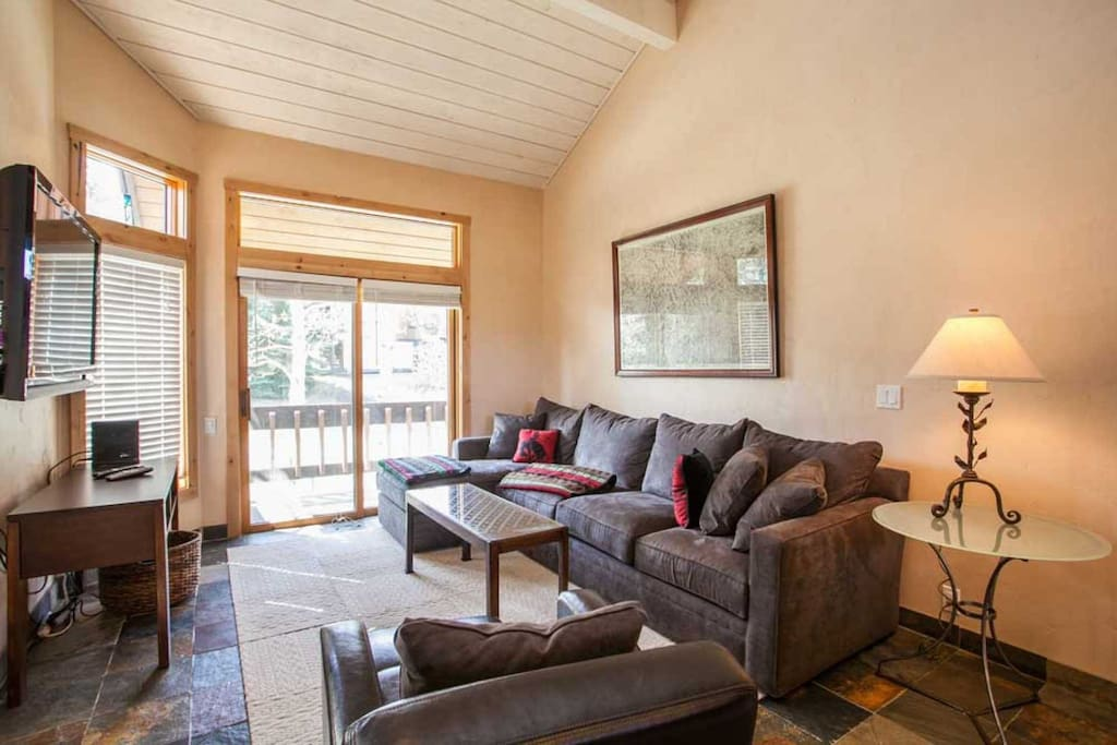 The living room is spacious and comfortable and features a gas fireplace and access to the deck.