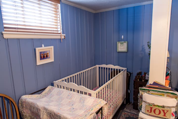 Crib and changing table! Please note, the crib is in back of the queen size bed and in the same room as the living area.