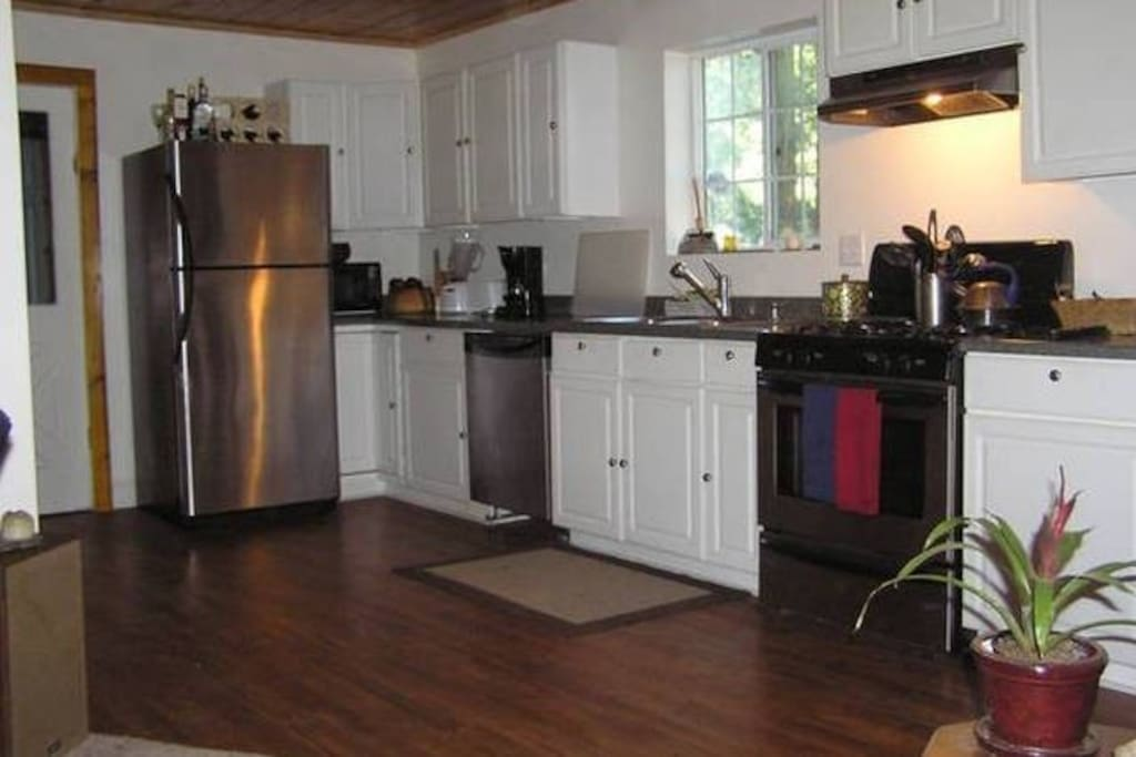 Kitchen with gas range, dishwasher, and big double basin sink.