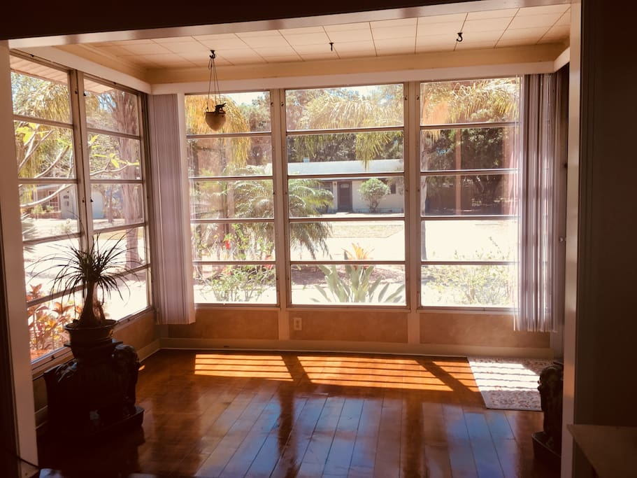Sun room is perfect for yoga, with wood floors and tinted windows for privacy.