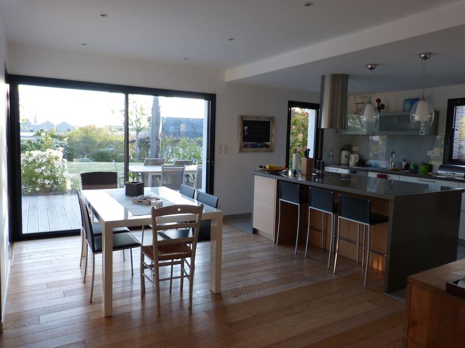 Salle à manger, cuisine ouverte, vue sur terrasse, piscine et jardin