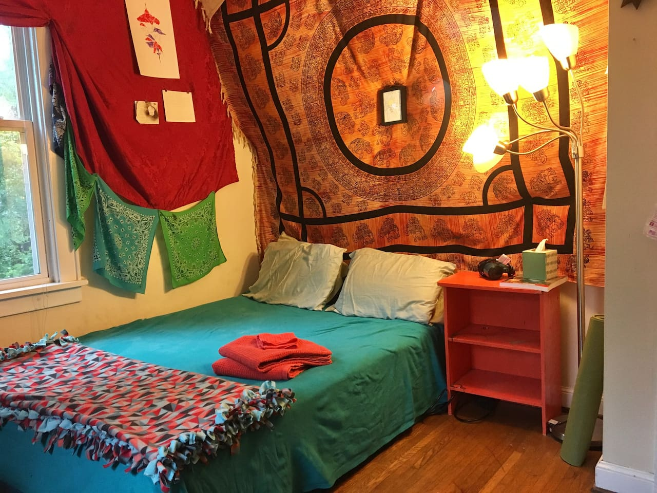 """Full sized bed with lamp and nightstand. The room is bright with a lot of personality. There's a hairdryer and a book of local day-hikes on the nightstand. There is also a yoga mat and (if you are around 5'4"""") a bike you can use during your stay (not pictured here)."""