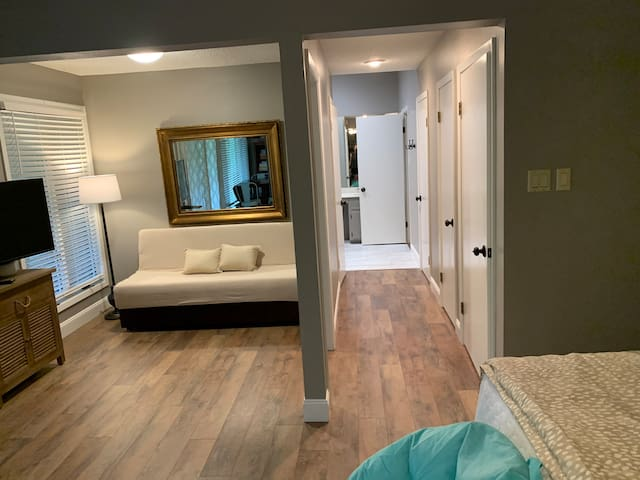 Lower level sitting alcove with futon and hall leasing into bathroom