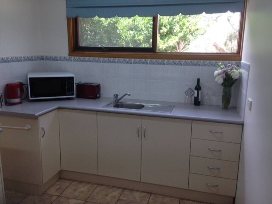 The kitchenette has a microwave, frypan, toaster and essential kitchenware.