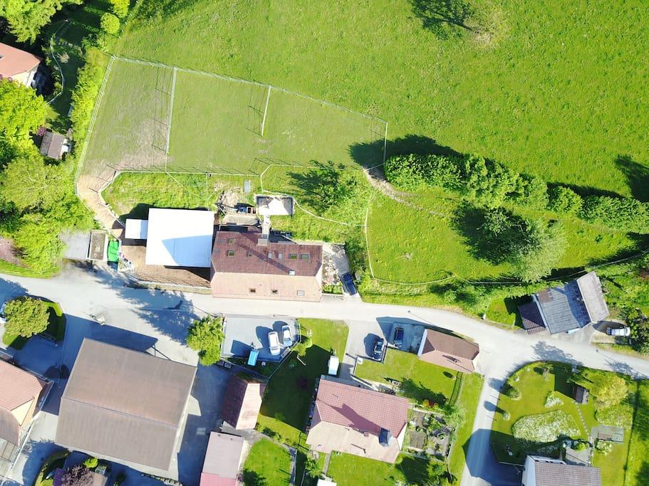 Luftaufnahme Bauernhaus mit Pferdestall, Parkplatz, Weide und Umgebung