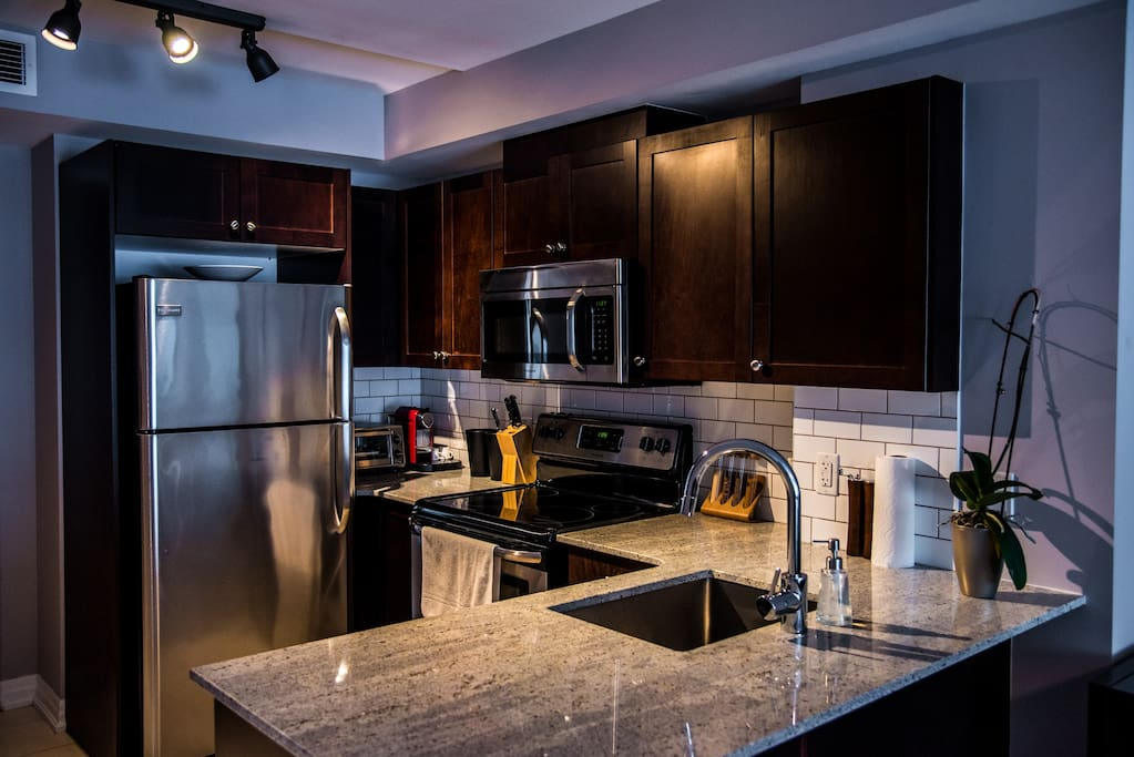 Granite and stainless steel in immaculate, fully appointed kitchen.