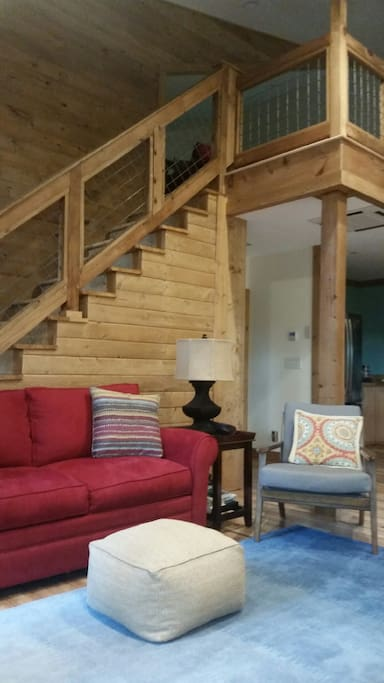 Spacious living room. Couch includes a full pull out bed. Stairs lead to the upstairs loft