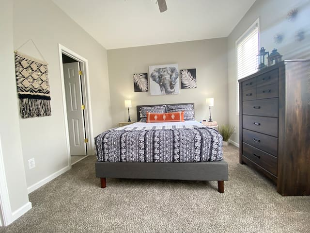 upstairs bedroom with queen bed with attached full bathroom
