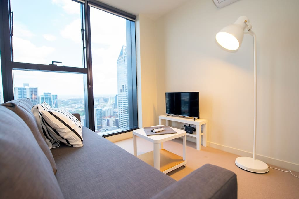A spacious TV lounge with a balcony & view.