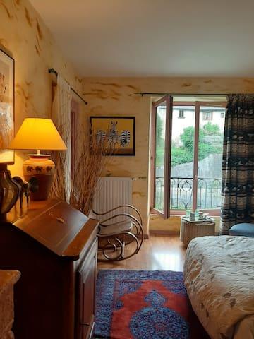 Chambre originale avec lit double et salle douche privative.