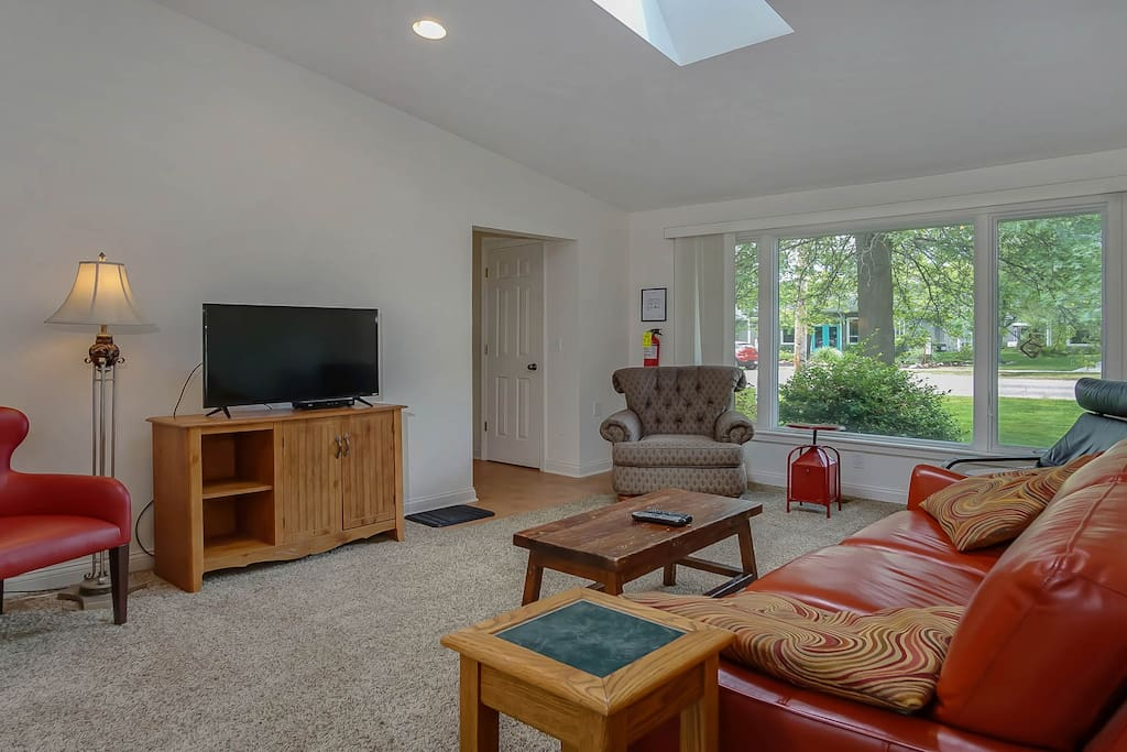 The living area features a flat screen TV and a large window.