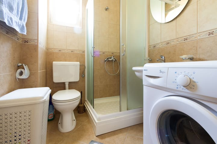 Bathroom with shower, laundry machine