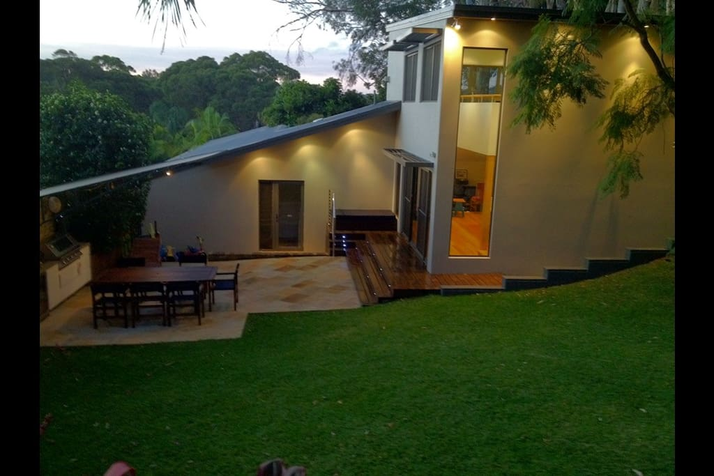 Open plan backyard party area with Stereo and Heaters. Stainless steel BBQ, large 2 door bar fridge, sink, and sunshade awning. Large wooden table with seats on Sandstone courtyard that leads into grass yard.