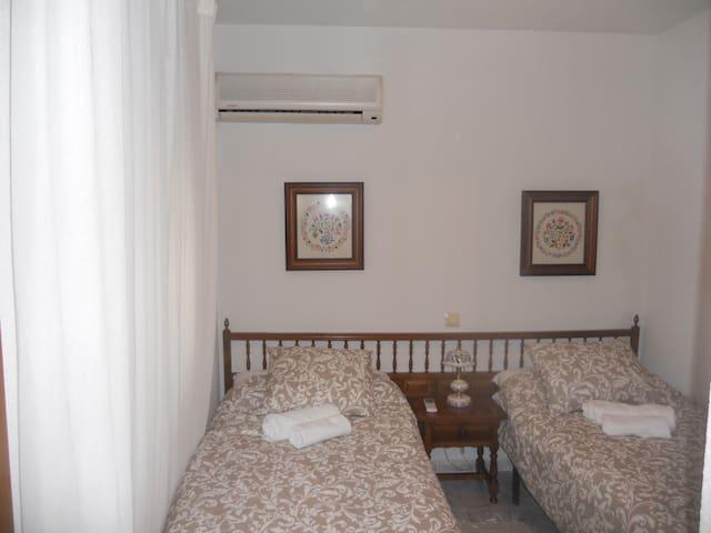 Habitación con dos camas (90cm, aire acondicionado con bomba de calor y armario).