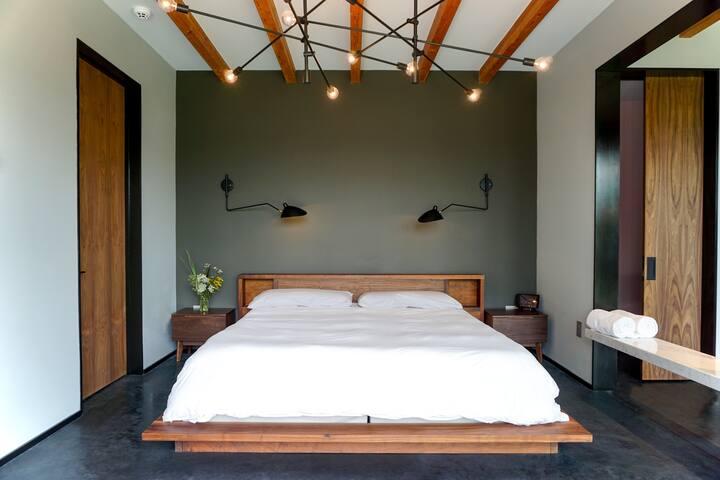 Master bedroom features custom designed king bed with en-suite bathroom.