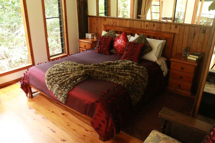 Queen bedroom downstairs with privacy curtains a rainforest view