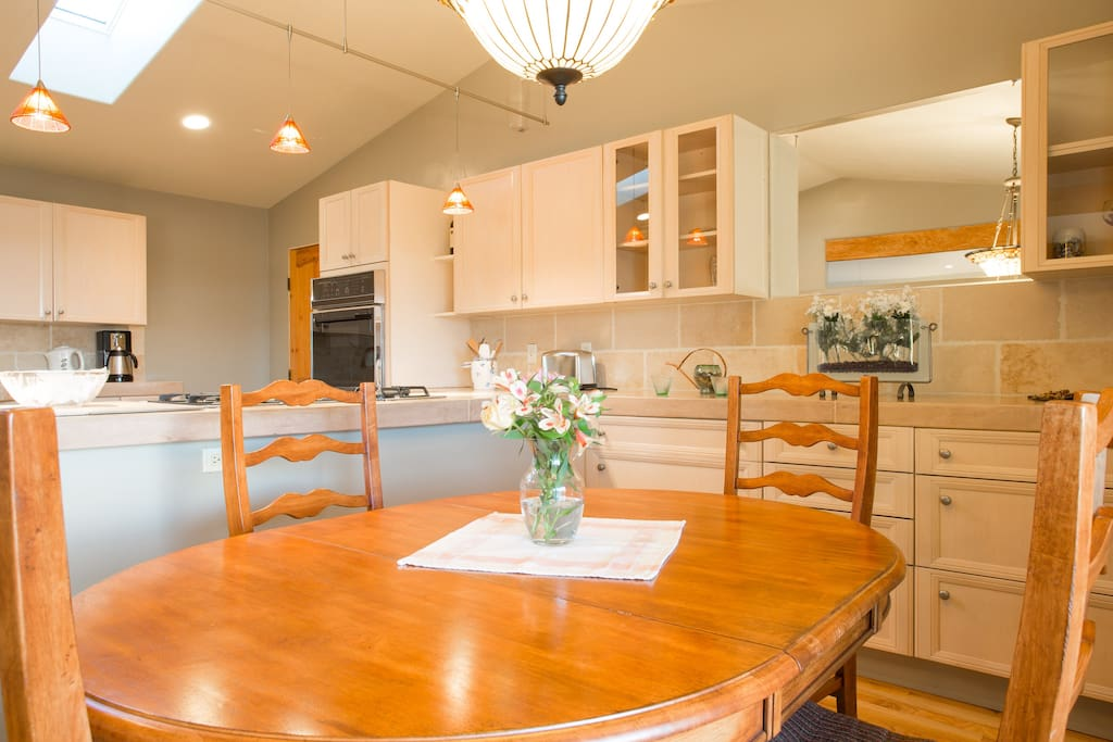 Dining room/kitchen area conducive to cooking and socializing.   Skylights and large  westward- facing windows provide light and view of bay/sunsets.