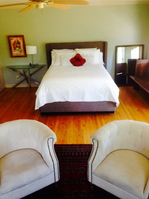 Large, bright, airy, ground floor master bedroom; glass doors open to garden. Room has hardwood floors and living space that includes couch, chairs, dressers and closet space.
