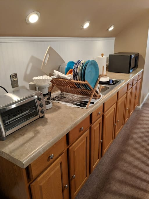 Enjoy a well-equipped kitchenette with a refrigerator,  coffee maker, microwave, toaster oven, and dishes.