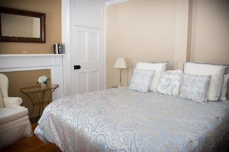 Windsor Guest Room with King bed and private bathroom, air conditioner/heating unit and television.