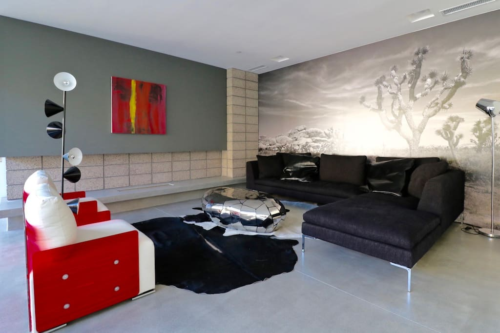 Stunning living room is surrounded by contemporary art and modern accents.