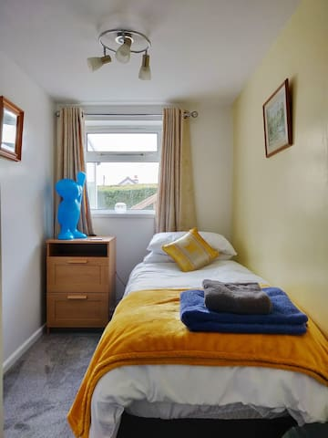 Small bedroom with comfortable single bed, bedside table and wardrobe.