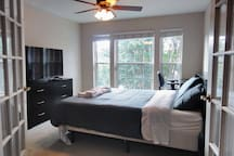 """Upstairs bedroom features a queen sized bed, 49"""" tv, work desk and beautiful tree-top windows!"""