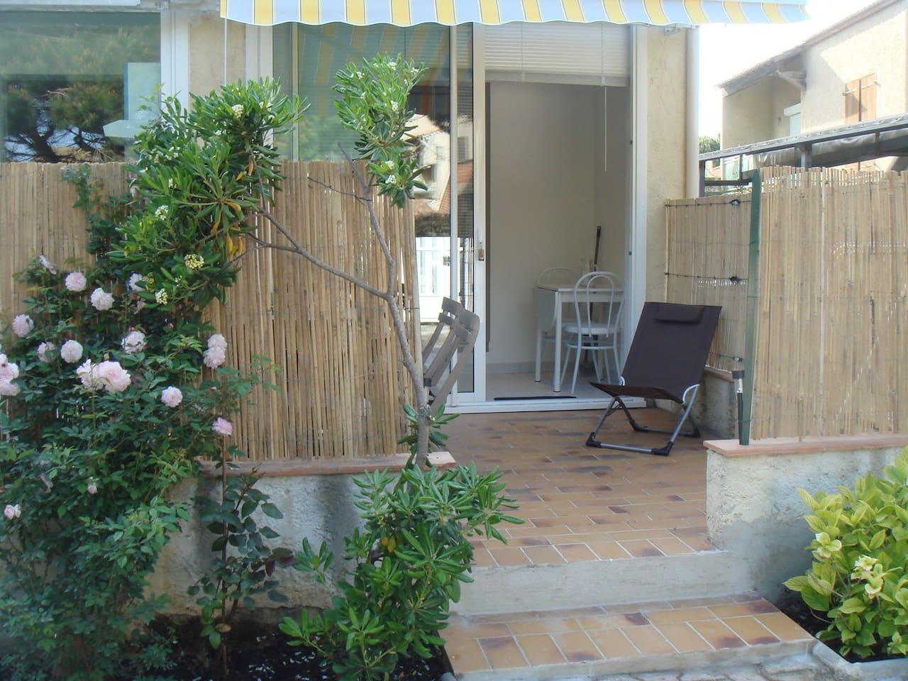 Extérieur du studio, terrasse, baie vitrée donnant sur la petite cuisine.