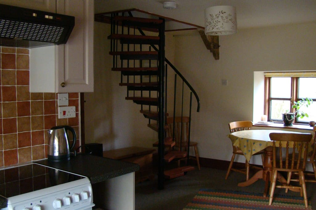 living space with spiral stairs leading to bedroom