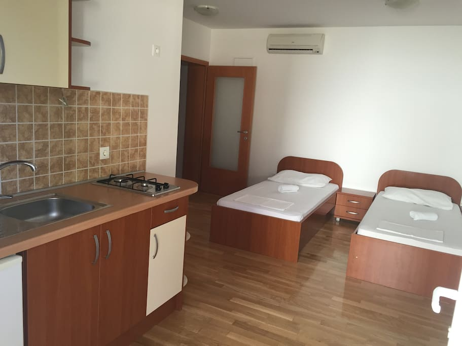 Fully equipped kitchen with living room. Two single beds and tv are in the living room.
