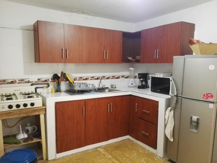 Kitchen with Fridge, coffee maker, microwave, blender, stove, dishes