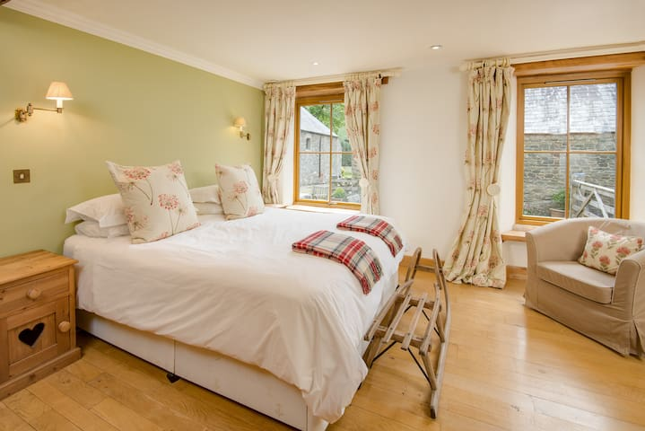 The Oak bedroom has a sumptuously comfortable bed with sitting space and lots of natural light