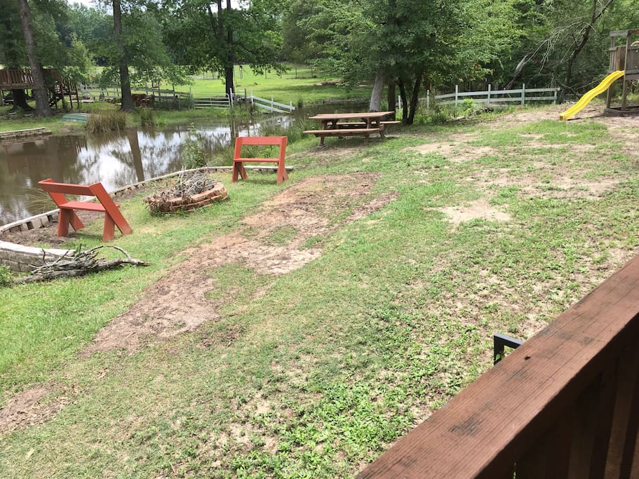 The side yard with fire pit, picnic table, and benches