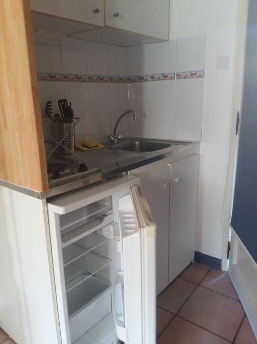 Coin cuisine avec frigo et plaque. Une cafetière est également disponible ainsi qu'une bouilloire