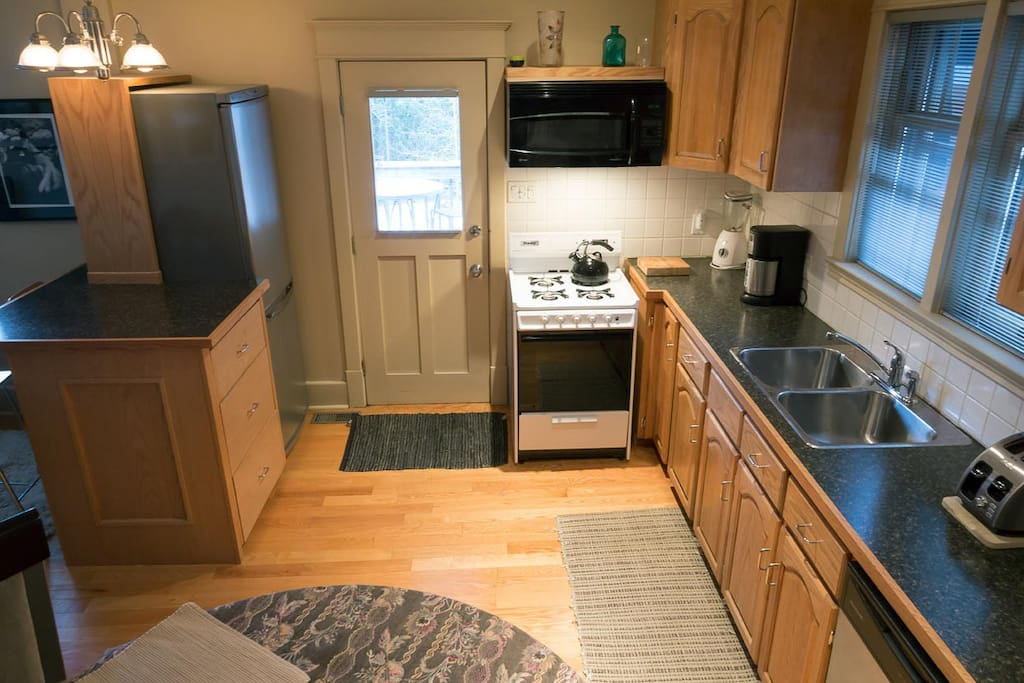 Kitchen with fridge/freezer, gas stove, double sink, dishwasher, convection/microwave/fan above stove. Gas barbecue just outside the door on deck.