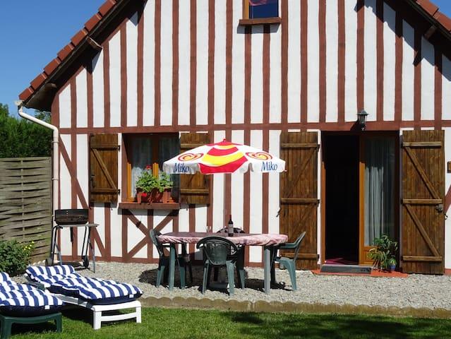 Salon de jardin, parasol, lits de soleil et barbecue sur la terrasse.