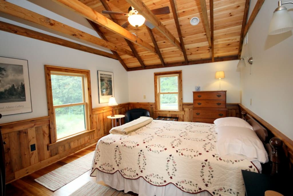 Upstairs bedroom with queen bed and cathedral ceiling.  Views of garden and distant mountains from window.